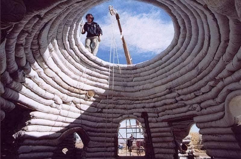 Поступово звужуючи кільцеву кладку з мішків, будівельники зводять купол
