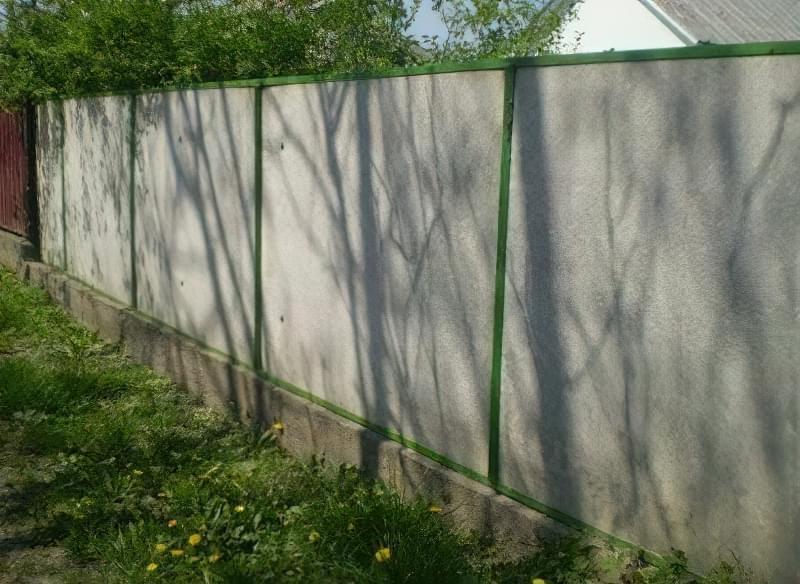 Зовнішній вид паркану з плоского шиферу з обрамленням з куточка і смуг