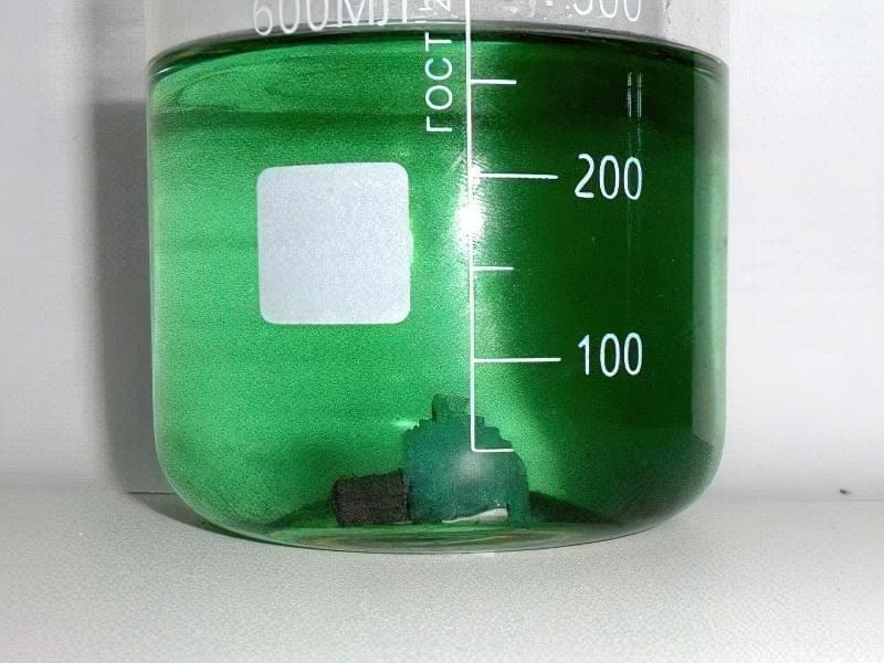 Кристал залізного купоросу в градуированном посудині з водою